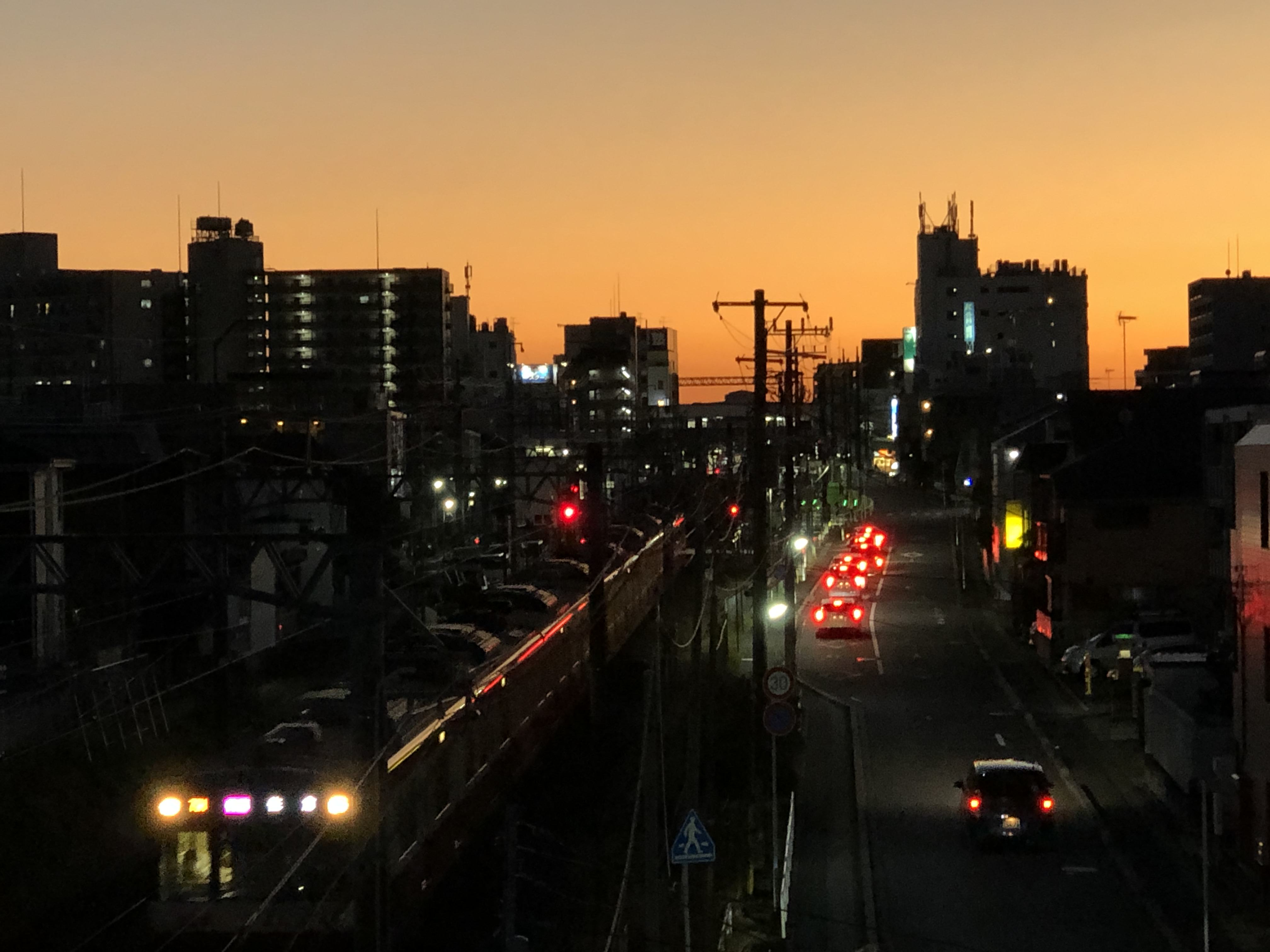 Picture of a city during the dusk with a train passing by and several vehicles on the road.